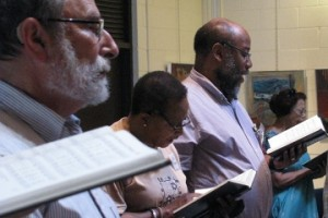 men and women standing with open hymnals