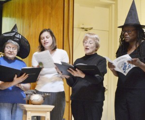 Four women, two in witch hats singing with choir music folders