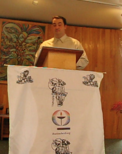 man standing behind wood pulpit with hanging in front with African decoration and Unitarian Universalist rainbow chalice made by Kenyan UUs in Ruai